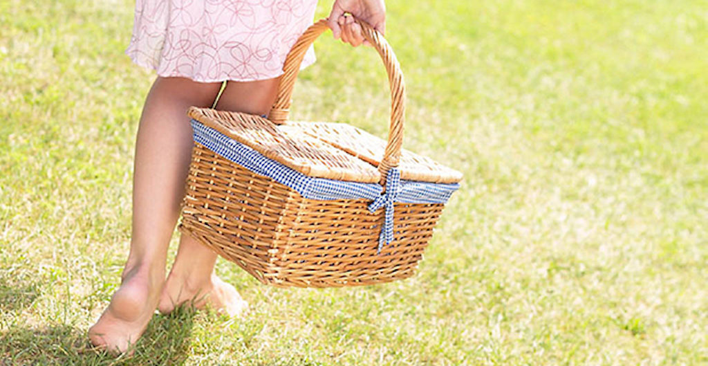 woman-walking-in-grass-with-picnic-basket-uid-1284832